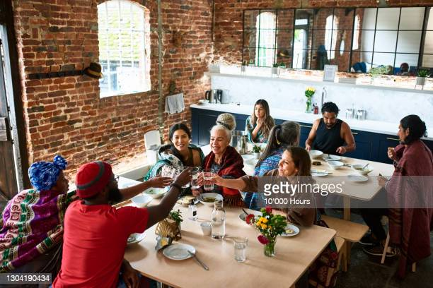 multi-ethnic friends in dining room having celebratory lunch - community stock pictures, royalty-free photos & images