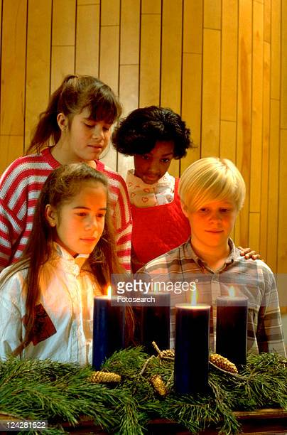 multi-ethnic friends looking at advent candles in church - junior girl models stock pictures, royalty-free photos & images