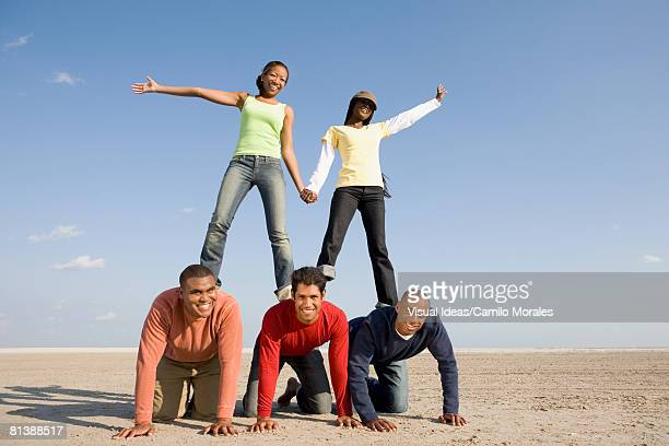 multi-ethnic friends making human pyramid - human pyramid stock photos and pictures