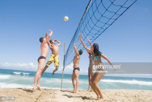 Multi-ethnic friends playing volleyball at beach