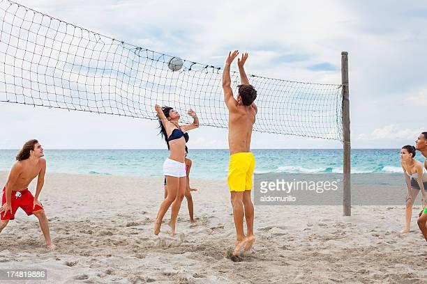 Multi-ethnischen Freunde spielen Sie volleyball am Strand.