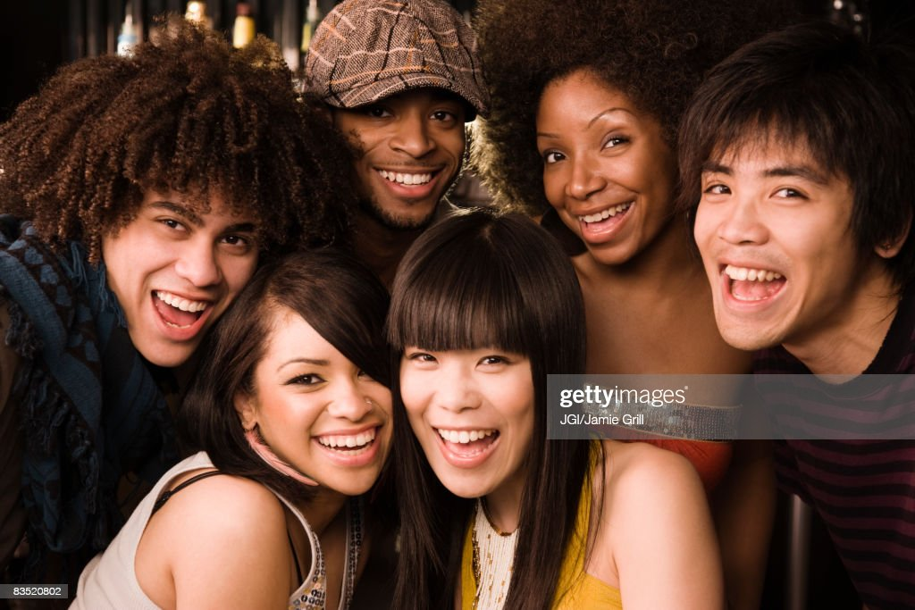 Multi-ethnic friends posing in nightclub : Stock Photo