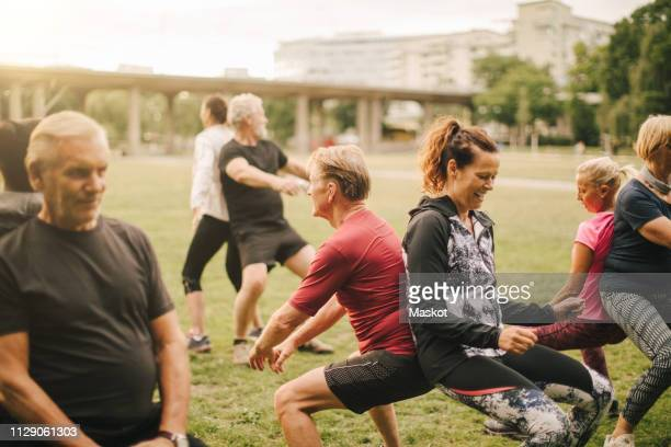 multi-ethnic friends practicing back to back squats in park - practicing stock pictures, royalty-free photos & images