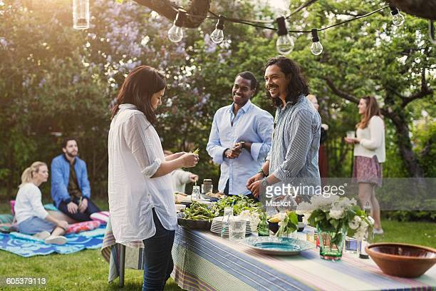 Multi-ethnic friends preparing food at dining table in backyard