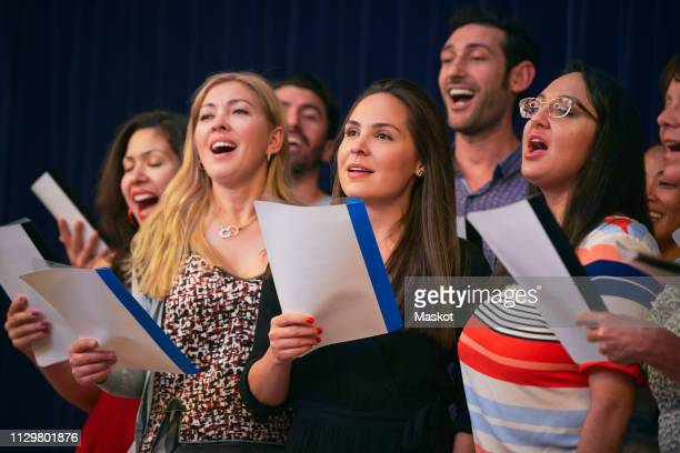multi-ethnic friends singing at choir practice in language school - choir stock pictures, royalty-free photos & images