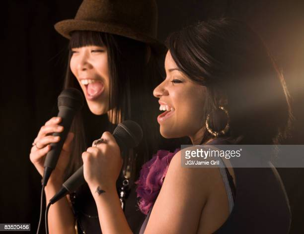 multi-ethnic friends singing karaoke - duet stock pictures, royalty-free photos & images