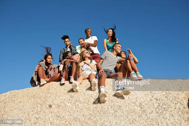 multi-ethnic friends sitting together on rock - generation z stock pictures, royalty-free photos & images