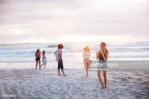 Multiethnischen Freunde stehen und spielt am Strand
