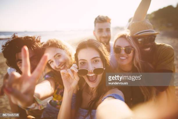 multi-ethnic friends taking selfies at the beach on summer holidays - young adult stock pictures, royalty-free photos & images