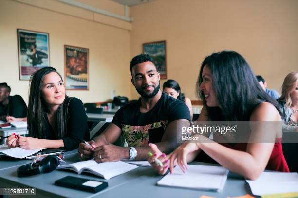 multi-ethnic friends talking while sitting at desk in classroom - emigration and immigration stock-fotos und bilder
