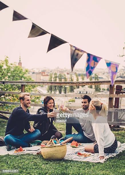 Multi-ethnic friends toasting elderflower drinks at rooftop party