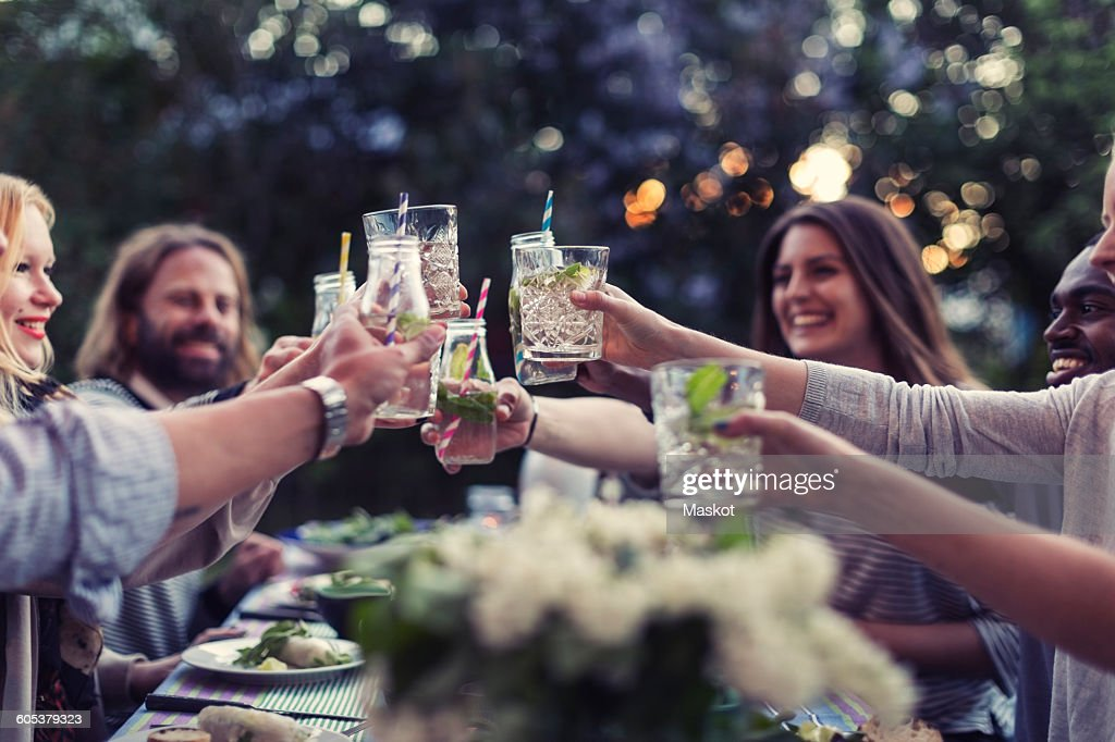 Multi-ethnic friends toasting mojito glasses at dinner table in yard : Stock Photo