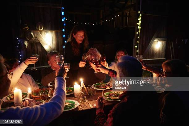 multi-ethnic friends toasting wineglasses at dinner party outside barn during night - brindisi bicchieri foto e immagini stock