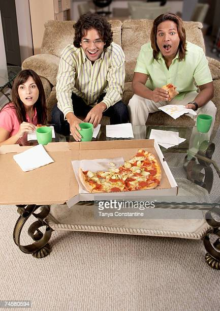 Multi-ethnic friends watching television and eating
