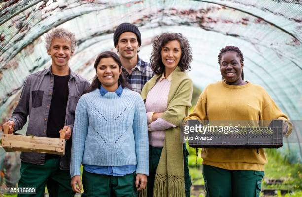 multi-ethnic garden workers standing in greenhouse - diversity stock pictures, royalty-free photos & images
