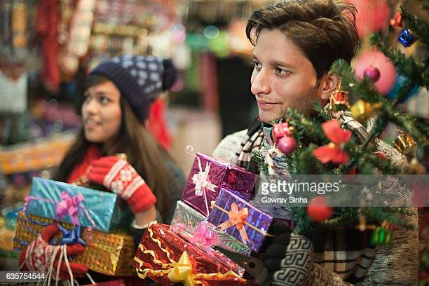 Multiethnic girl and boy in market shopping for Christmas.