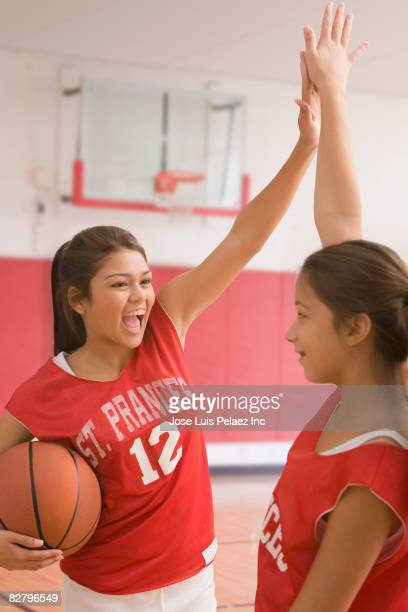 Multi-ethnic girls high-fiving in basketball uniforms