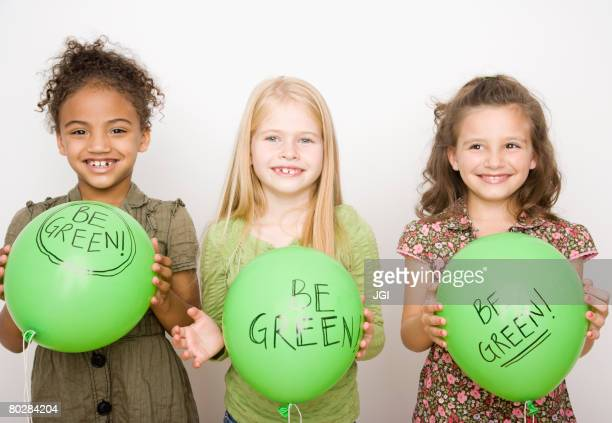 multi-ethnic girls holding green balloons - campaigner stock pictures, royalty-free photos & images