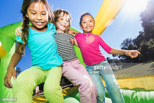 multi-ethnic girls jumping together on bounce house - castle stock pictures, royalty-free photos & images