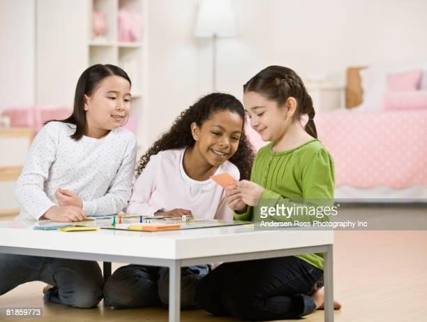 Multi-ethnic girls playing board game