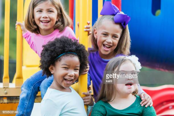 multi-ethnic girls playing on playground - down syndrome stock pictures, royalty-free photos & images