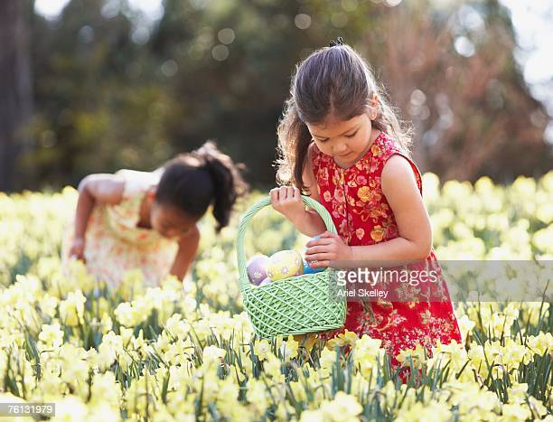 multi-ethnic girls searching for easter eggs - chasse aux oeufs de paques photos et images de collection