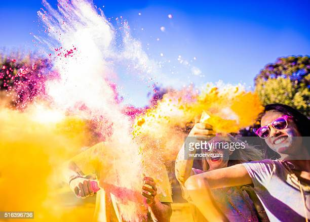 multi-ethnic group celebrating holi festival in park - holi stock pictures, royalty-free photos & images