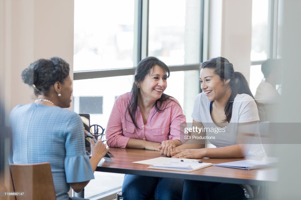 Multi-ethnic group engage in conversation of starting a bank account : Stock Photo