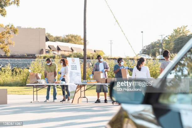 multi-ethnic group finishes sorting food to give away - giving tuesday stock pictures, royalty-free photos & images