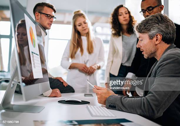 Multi-ethnic group having a quick team meeting at desk