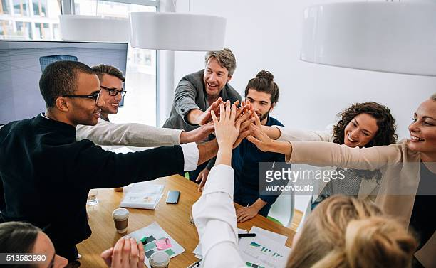Multi-ethnic group high five after successful cooperation and teamwork