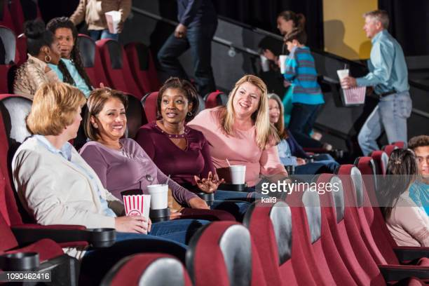 multi-ethnic group in a movie theater, getting seated - girlfriends films stock pictures, royalty-free photos & images