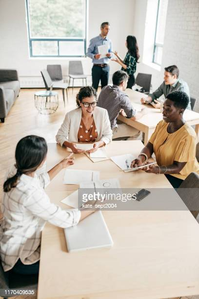 multi-ethnic group negotiating  in a coworking space - employee engagement stock pictures, royalty-free photos & images
