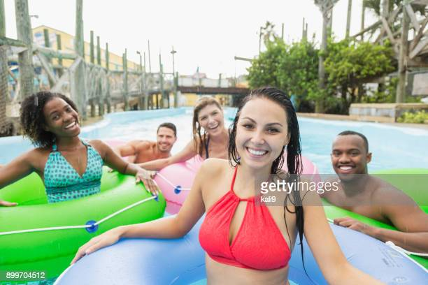 multi-étnica grupo de amigos adultos nos anéis infláveis - homens de idade mediana - fotografias e filmes do acervo