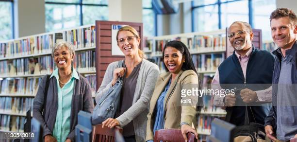 multi-ethnic group of adults standing in library - istruzione post secondaria foto e immagini stock