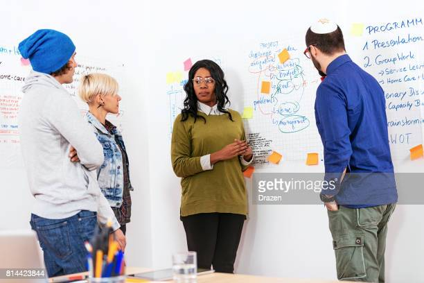 Multi-ethnic group of adults working together in office on project development