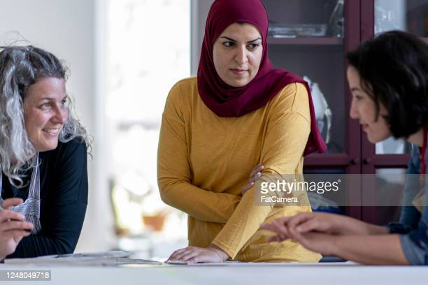 multi-ethnic group of artists reviewing design plans for a textile project - showus stock pictures, royalty-free photos & images