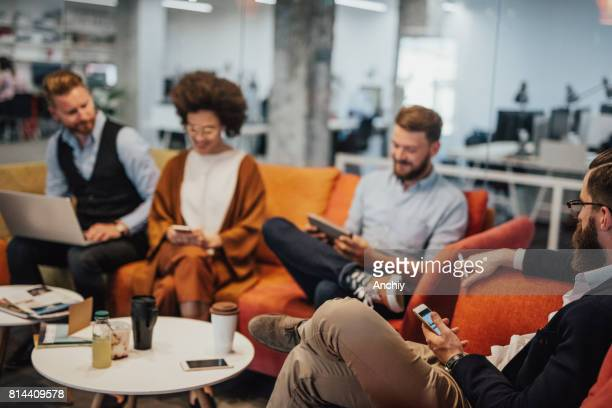 Multi-ethnic group of businesspeople drinking coffee during break