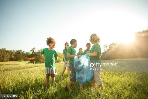 multiethnic group of children collecting waste. - questão ambiental imagens e fotografias de stock