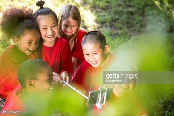 multiethnic group of children enjoying school trip - teamevenement stockfoto's en -beelden
