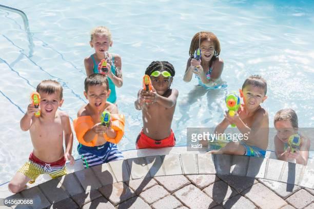 Groupe multi-ethnique d'enfants dans la piscine avec des fusils squirt