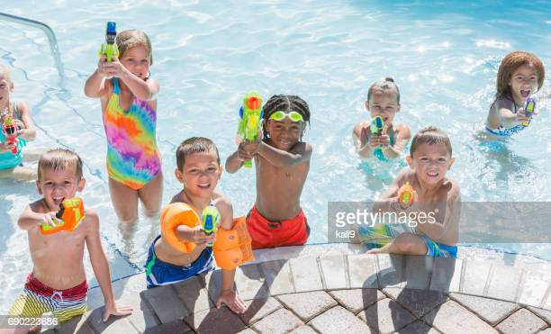 multi-ethnic group of children in pool with squirt guns - kids pool games stock pictures, royalty-free photos & images
