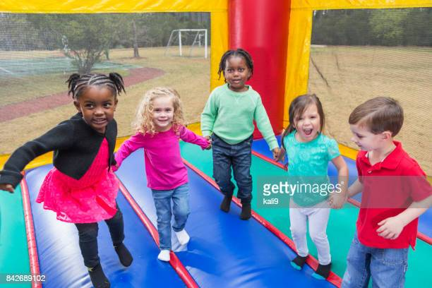 Multi-ethnic group of children jumping in bounce house