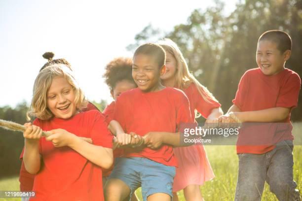 multiethnic group of children playing with rope. - nur kinder stock-fotos und bilder