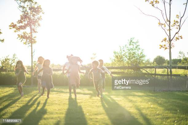 multi-ethnic group of children running in the sunlight stock photo - fatcamera stock pictures, royalty-free photos & images