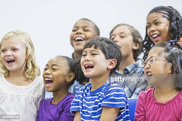 multi-ethnic group of children sitting together shouting - girl sitting on boys face stock photos and pictures