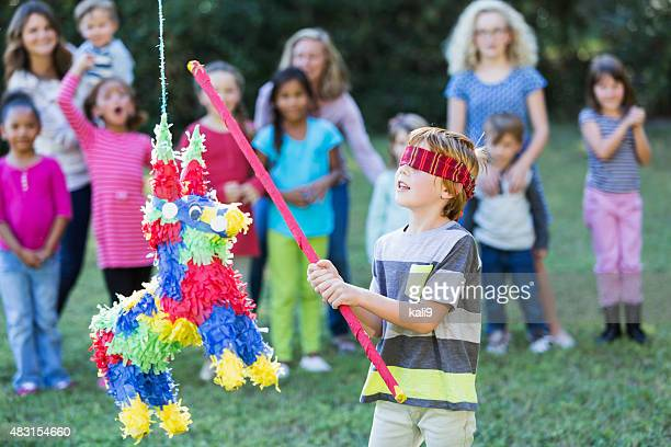 multi-ethnic group of children with boy hitting pinata - pinata stock pictures, royalty-free photos & images