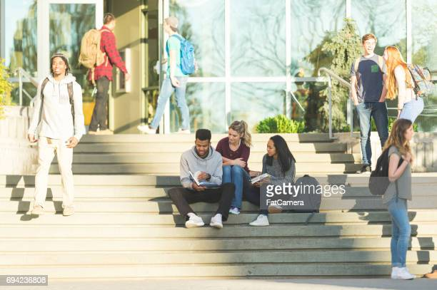 Multiethnic group of college students hang out at lunch together and wait for their next class to start