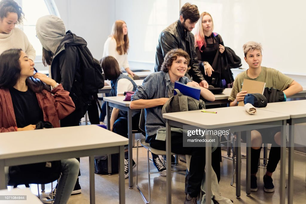 Multi-ethnic group of College students leaving classroom. : Stock Photo