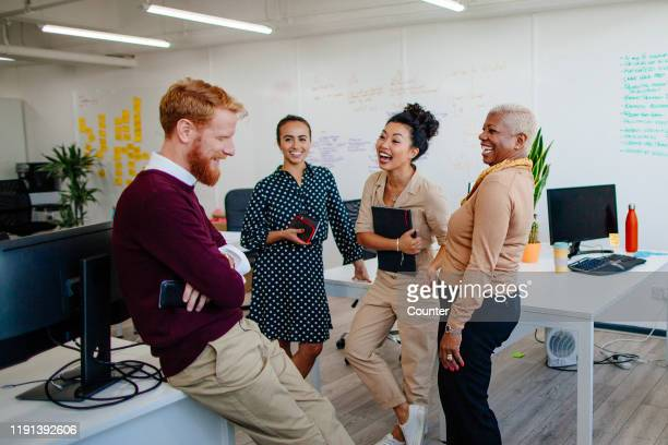 multi-ethnic group of coworkers laughing together at the office - working seniors stock pictures, royalty-free photos & images
